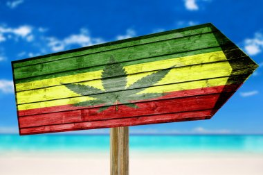 Rasta Flag With Marijuana Leaf wooden sign on beach background