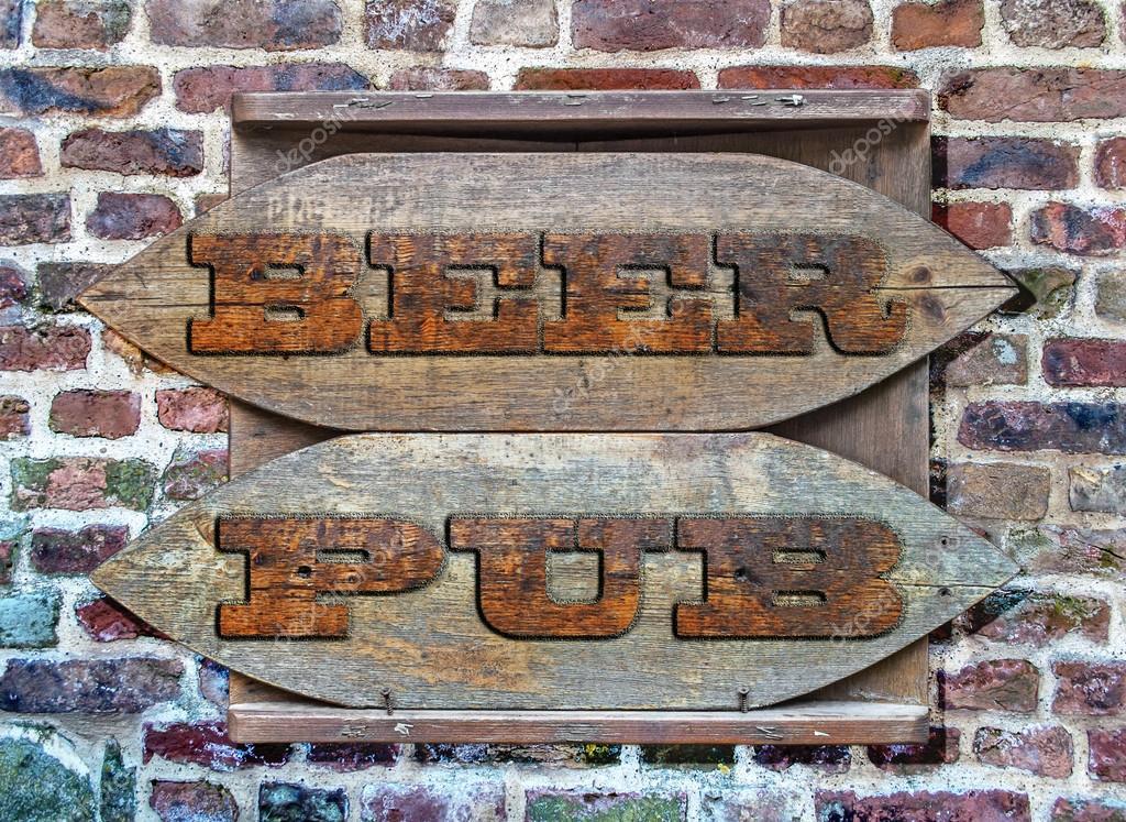 Segno di birra pub legno appeso sul muro di mattoni for Disegni di garage di mattoni
