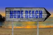 Photo Nude Beach wooden sign with on a beach background