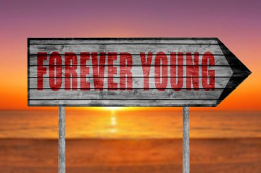 Red Forever Young sign with on beach background