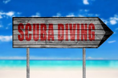 Red Scuba Diving wooden sign with a beach on background