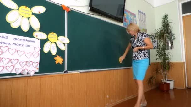 Učitel zapisuje domácí úkoly