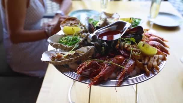 Gekochte gemischte Meeresfrüchte mit Salver, Hummergarnelen, Riesengarnelen, Miesmuscheln, Austern und Tintenfischen werden auf einem Tisch für Restaurantbesucher serviert. Traditionelle meditative Schüssel auf Tablett.