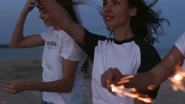 Freundinnen, die spazieren gehen, tanzen, sich bei nächtlichen Partys am Meer mit Wunderkerzen in der Hand amüsieren. Junge Teenager-Frauen feiern am Strand mit Feuerwerk und Bengalischen Lichtern. Mädchen in Zeitlupe, Standbild.