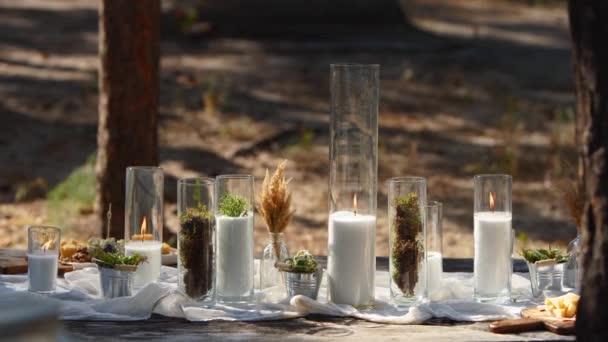 Svatební hostina venku v lese. Jídelní stůl zdobený ve stylu boho se svíčkami, bílou látkou, květinami, servírovaný s talíři, stolním nádobím, nádobím, jídlem, stemware a nápoji. Rekreační stravování.