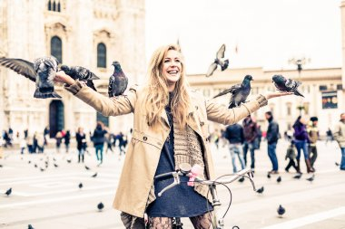 Woman playing with pigeons
