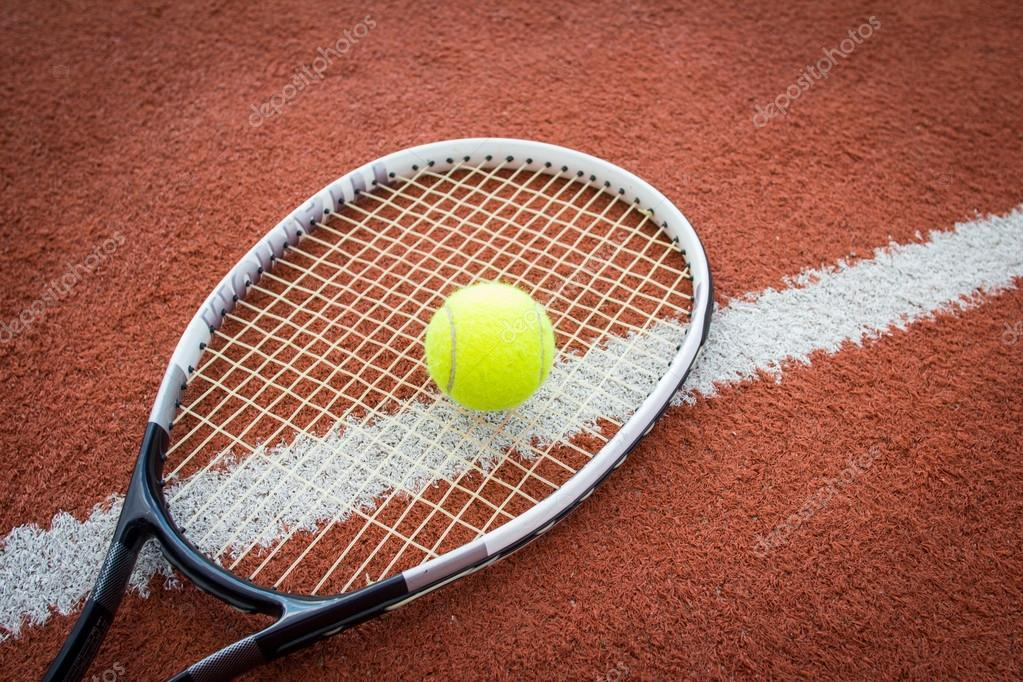 f6e69ac009 Uma raquete de tênis preto e branco perto de uma bola amarela numa quadra  de tijolo vermelho — Fotografia por mrstam