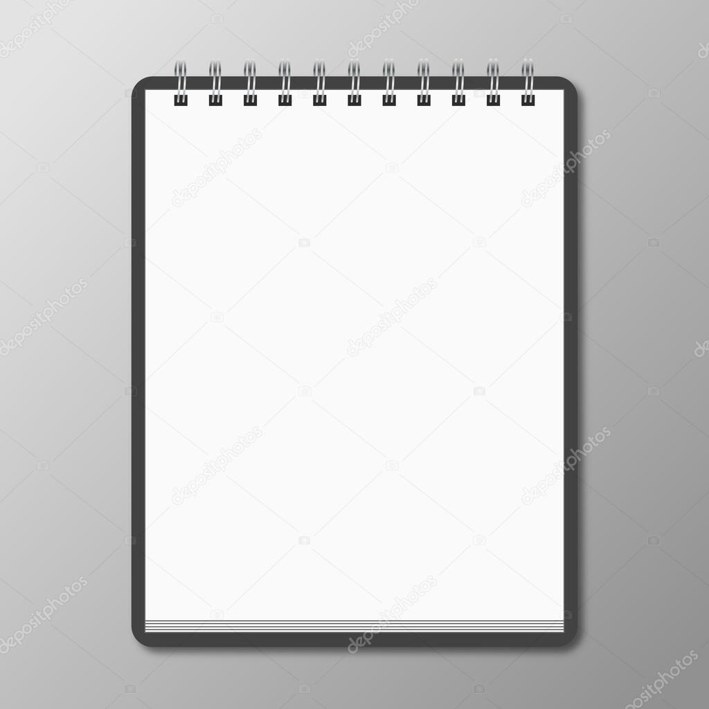 Blank spiral notebook on white background with soft shadows.