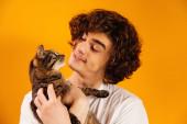 Kudrnatý muž se usmívá při pohledu na kočku izolovanou na oranžové