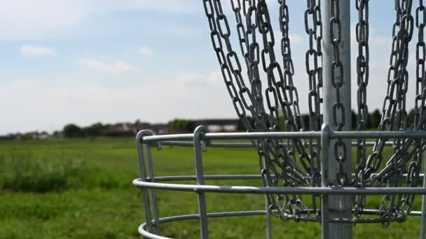 Disc golf goal chains gently swaying in the breeze with a green course in the background