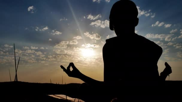 Silhouette of a Boy on the Background of Sunset Meditating Sitting