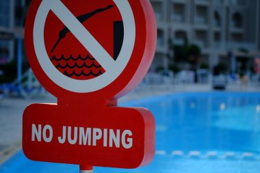 Red no jumping warning sign at the poolside