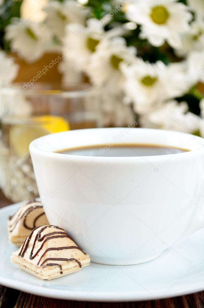 coffee with candies, lemon water and white flowers