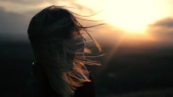 Szép lány nézni a naplementét és a mosolygó, napkitörés
