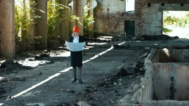architect builder engineer builder of ruined building looking girl work plan for the construction site construction plan explains in helmet construction helmet girl looks architectural plan and