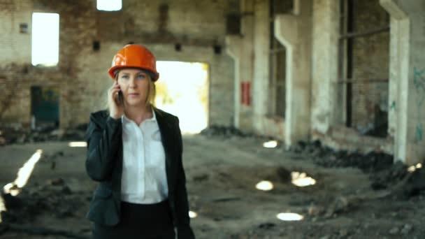 Architekt Bauunternehmer Ingenieur Bauunternehmer ruinierte Gebäude aussehende Mädchen Arbeitsplan für die Baustelle Bauplan erklärt in Helm Bau Helm Mädchen sieht architektonischen Plan und