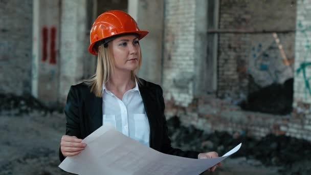 Architekt Baumeister Ingenieur Baumeister des zerstörten Gebäudes Arbeitsplan Mädchen auf der Suche nach der Bauplan für Website-Bau im Helm Bau Helm Mädchen erklärt sieht Bauplan und