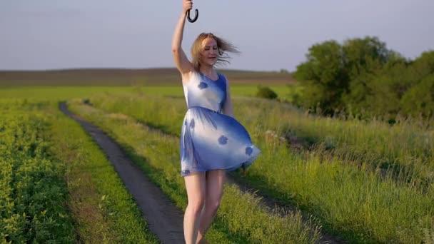 Ritratto di una bella ragazza con un ombrello rosso nel tramonto emozioni verde erba campo sorridente ragazza sorridente ballare ridere filatura tramonto ora dorata