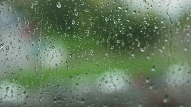 Dešťové kapky stékají po okenní tabuli v deštivém dni
