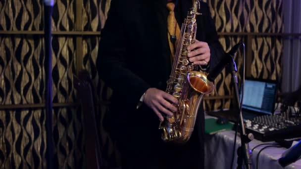 Zenész játszik a szaxofon, a koncert. Közelkép ujja nyomva az eszköz