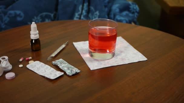 prášky a teploměr na stůl