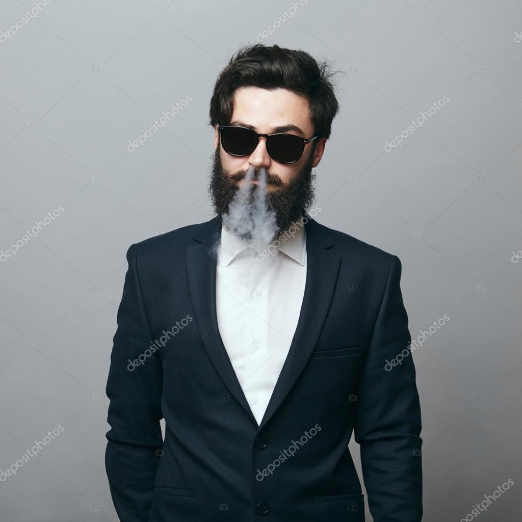 Robuste et viril. Young confiant barbu homme vêtu d un costume noir et  lunettes de soleil en regardant avec confiance caméra et exhalant la fumée  — Image de ... 9c958b57b511