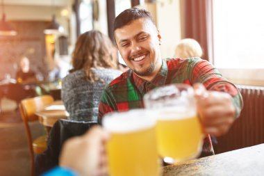 First person portrait of a young men drinking beer in a pub