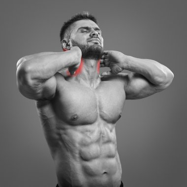Muscular man suffering from neck pain.