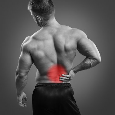 Muscular man with back pain over gray background.