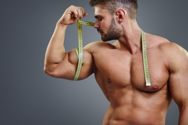 Bodybuilder measuring biceps with tape measure