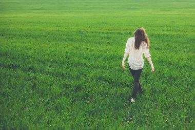 Back view of teenage girl in meadow