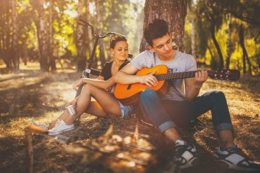Teenage couple having a picnic and playing guitar
