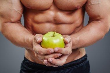 shirtless bodybuilder holding an apple