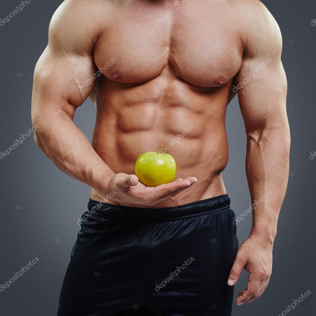 Shirtless muscular man holding a fresh apple