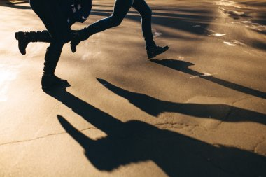 Abstract shadows of running couple on street