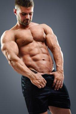 Bodybuilder man showing his abs