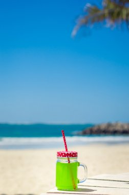 Vertical photo of green juice in a funny glass with a red straw, beach as background
