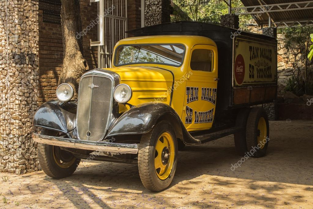 Yellow old model Chevrolet pickup truck in the patio of ancient cafe ...