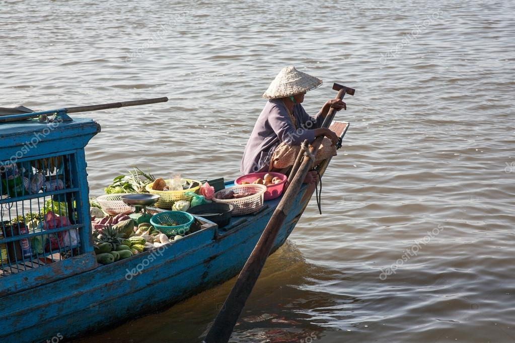 The woman with the paddle boat runs, bowls and baskets loaded with vegetables and fruits on the Tonle Sap lake in Cambodia.