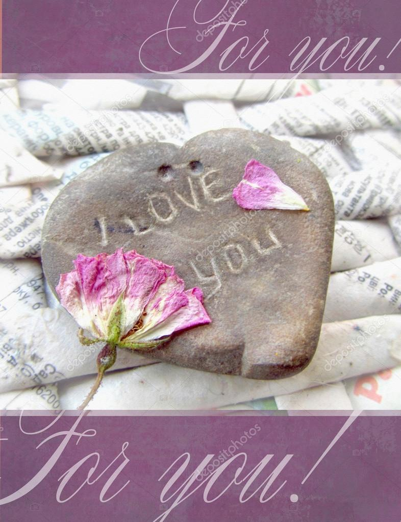 Greeting card. Stone in form of heart with the words I Love You and dried flower on a textured background of twisted interwoven newspapers.