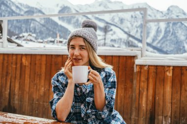 Portrait beautiful sexy blond woman wearing knitting hat and holding hot drink mug outdoor on a wooden terrace in winter mountains