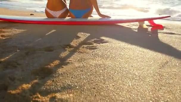 Surfer girls looking at ocean beach sunset.