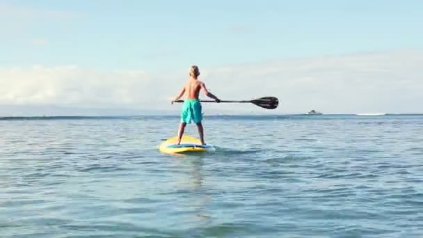 Young Blonde Surfer Boy Stand Up Paddling.
