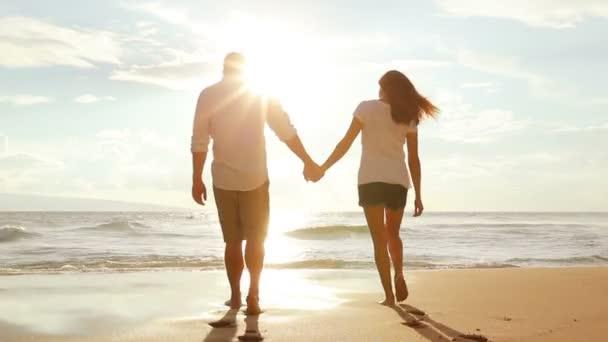 Séta a tengerparton napnyugtakor kézenfogva a szép fiatal pár