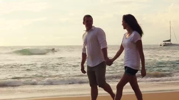 Beautiful Newlywed Couple Walking on Beach Holding Hands at Sunset