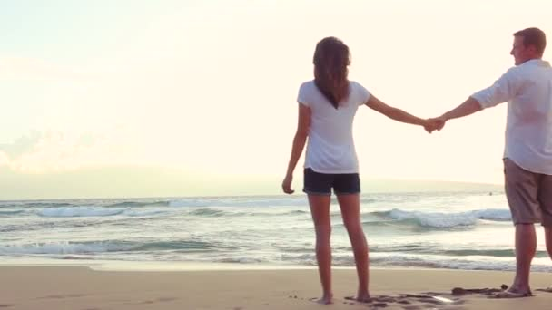 Beautiful Young Couple Holding Hands at Beach Sunset
