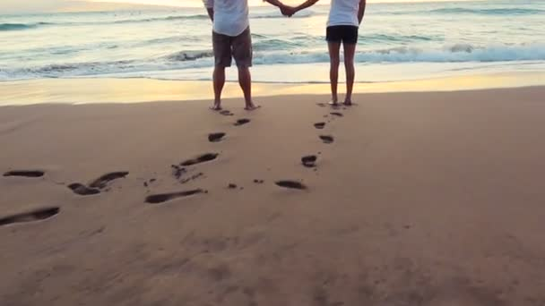 Cute Young Couple Holding Hands Watching Amazing Sunset on Beach Honeymoon in Hawaii