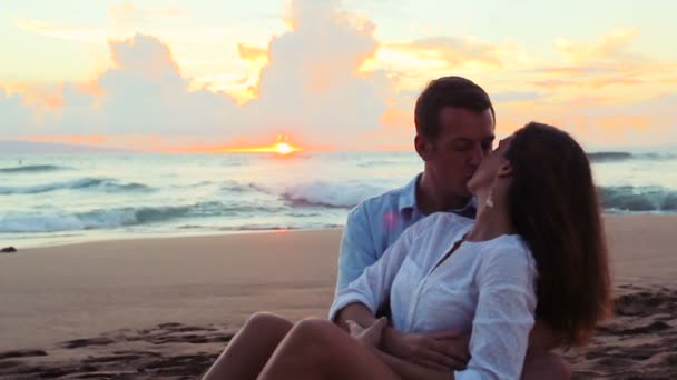 Beautiful Young Couple Sitting together Kissing at Beach Sunset