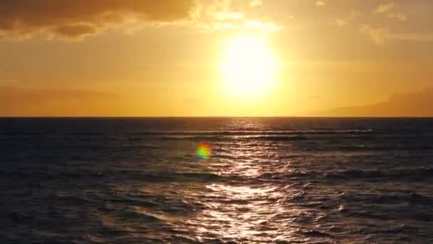Sun sets into the horizon above the ocean in Hawaii