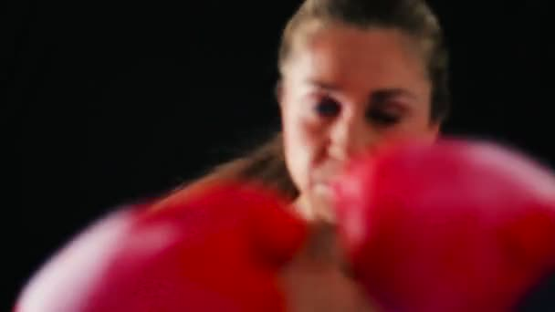 Beautiful Young Female Athlete Exercising for Self Defense with Boxing Gloves and Body Bag.